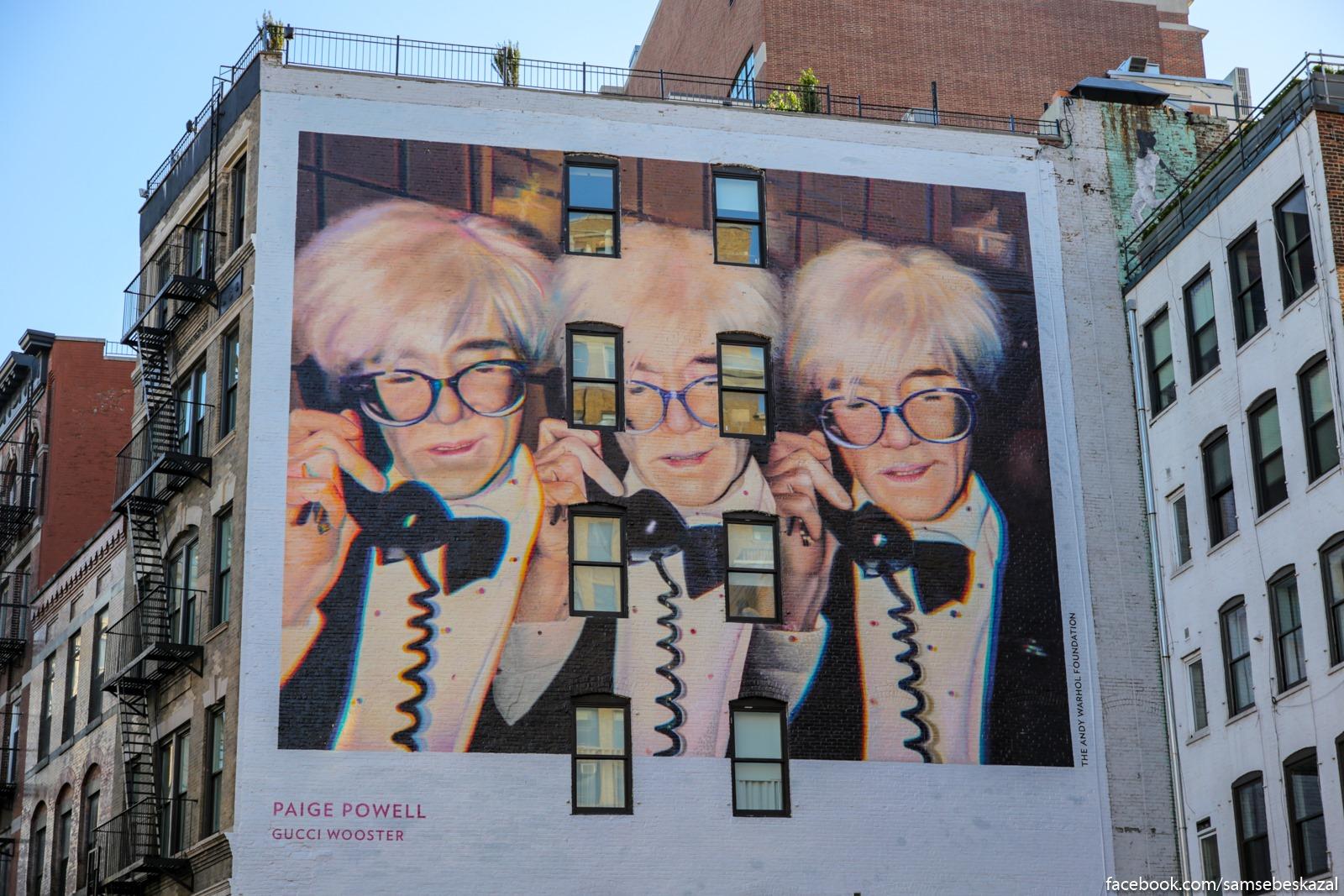 Risovannaa reklama posvasennaa vypusku serii fotoalʹbomov Pejdz Pauell na stene GucciArtWall v Manhettene.