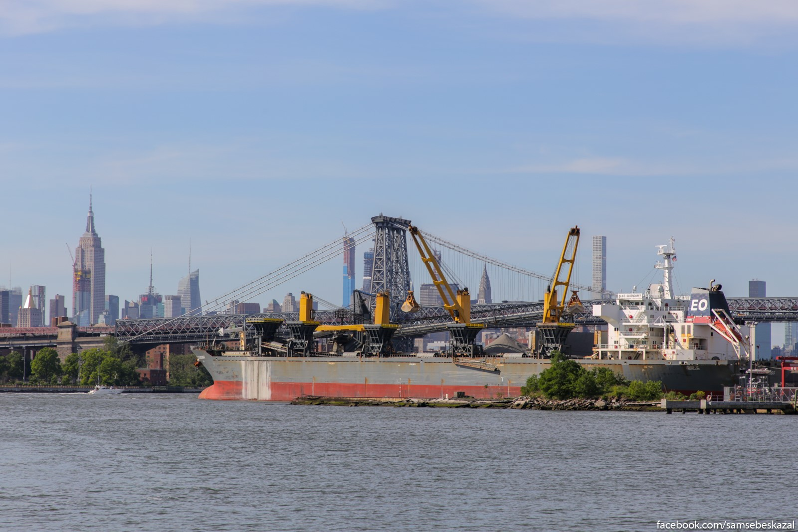 Okeanskij suhogruz na fone Uilʹamsburgskogo mosta i nʹu-jorkskih neboskrebov. Bruklin Nevi-Ard.